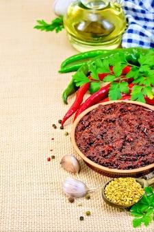 粘土カップのタバスコアジカ、さまざまな唐辛子、ニンニク、パセリ、フェヌグリーク、ナプキン、袋布のカラフの油