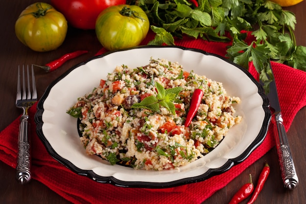 Tabbouleh - middle eastern vegetarian dish with couscous, tomatoes, parsley, dried raisins and mint seasoned with olive oil and lemon juice. easy authentic recipe