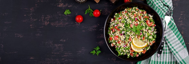 Tabbouleh salad. traditional middle eastern or arab dish. levantine vegetarian salad with parsley, mint, bulgur, tomato. banner.