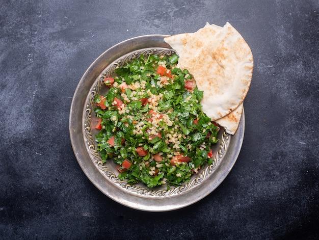 タブーラサラダ、伝統的な中東料理またはアラブ料理。通常、パセリ、ミント、ブルガー、トマトを使用しています。黒の背景