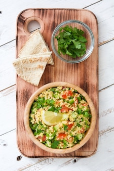 Tabbouleh salad with couscous in bowl on rustic white table top view