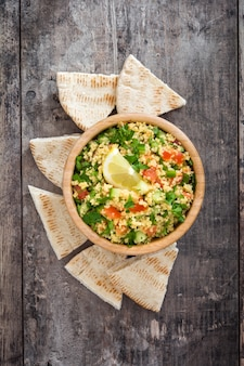 Tabbouleh salad with couscous and pita bread on a rustic table