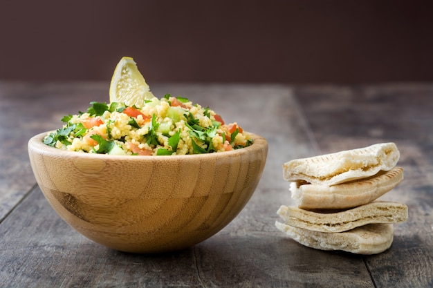 Tabbouleh salad with couscous and pita bread in wooden bowl on rustic table