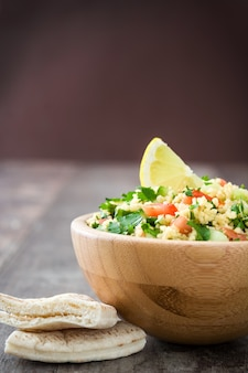 Tabbouleh salad with couscous in wooden bowl on rustic table