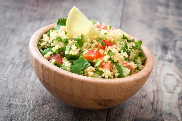 Tabbouleh salad with couscous on wooden table