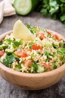 Tabbouleh salad with couscous on a wooden table