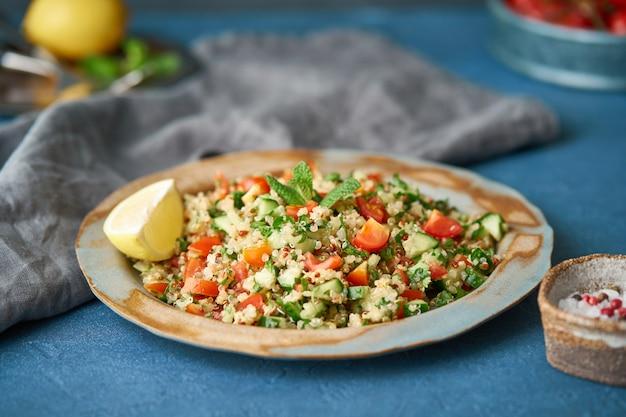 Tabboulehのキノアサラダ。東洋料理と野菜のミックス、ビーガンダイエット。側面図、古いプレート