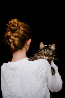 A tabby cat sits on a shoulder on a black background.taking care of a pet.