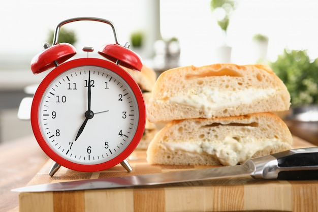 Table an alarm clock and breakfast bread and sauce