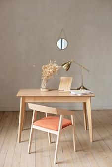 ベージュ色のモダンなスタイルのテーブルと椅子、花瓶と銅のランプ。ホームオフィス。インテリア・デザイン。