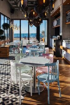 Стол и стулья в стильном интерьере кафе в винтажном стиле, с большими окнами и видом на море