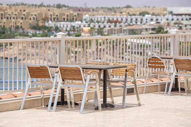 이집트 샤름 엘 셰이크(sharm el sheikh)의 홍해 옆 해변 카페에 있는 테이블과 의자가 닫혀 있습니다.