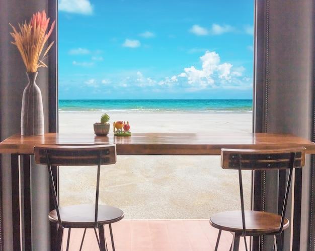 바다 전망 창 앞의 테이블과 의자.