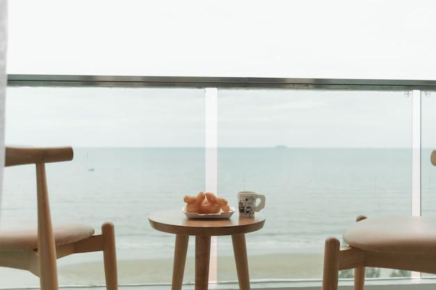 Стол и стулья на балконе с летней концепцией с видом на море