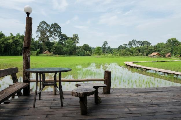 나무 발코니에 있는 테이블과 좌석은 곡선형 나무 보도와 농부 오두막이 있는 논 농장을 볼 수 있는 태국 나콘 나욕(nakhon nayok)입니다. 에서 유명한 경치 좋은 여행 랜드마크 또는 휴가 메이커.