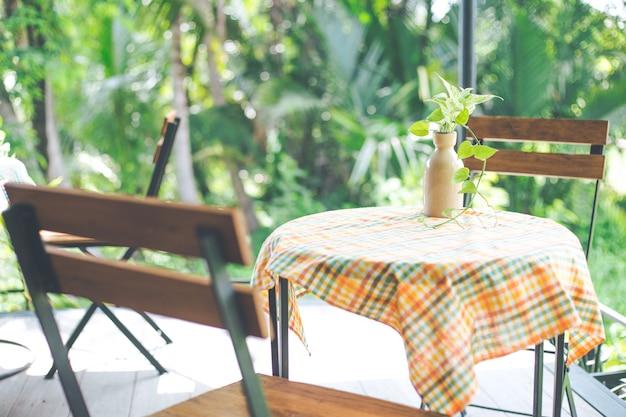 カラフルなテーブルクロスを備えた喫茶店のテーブルトップに鉄製のテーブルと木製の椅子