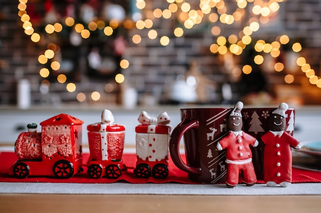 On the table are beautiful mugs, as well as kitchen utensils in the form of a train. the kitchen is decorated for christmas. next to the mugs is a ginger cookie in the form of men in a santa costume.