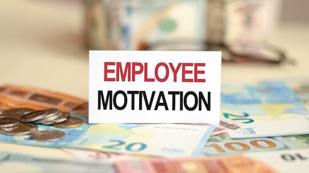 On the table are bills, a bundle of dollars and a sign on which it is written - employee motivation. finance and economics concept.