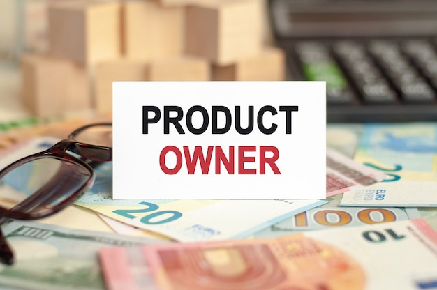 On the table are bills, a bundle of dollars and a sign on which it is written - product owner