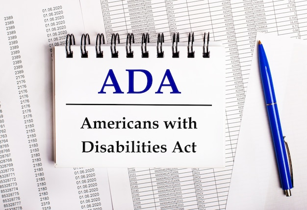 On the table are charts and reports, on which lie a blue pen and a notebook with the word ada americans with disabilities act