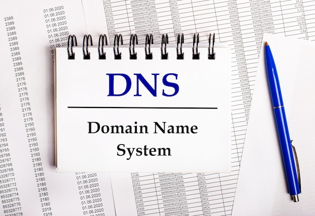 On the table are charts and reports, on which lie a blue pen and a notebook with the word dns domain name system