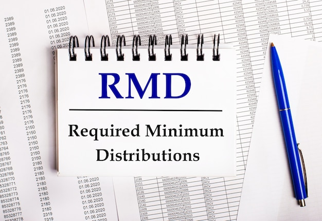 On the table are charts and reports, on which lie a blue pen and a notebook with the word rmd required minimum distributions.