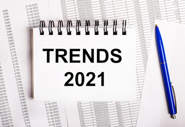 On the table are charts and reports, on which lie a blue pen and a notebook with the word trends 2021