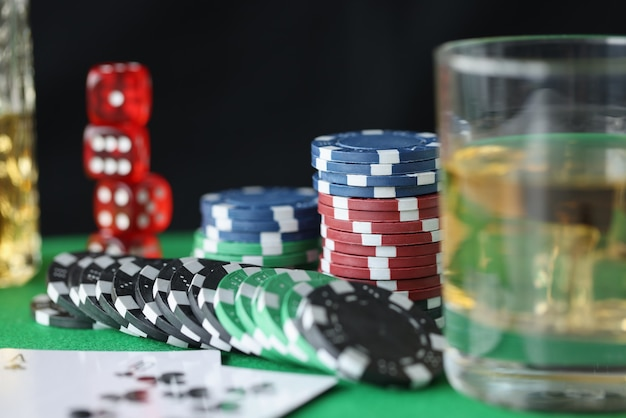 On table are chips for casino cards and glass of alcohol. gambling addiction concept