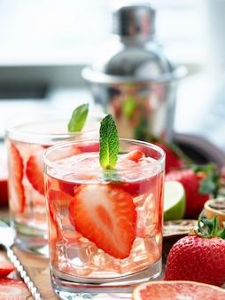 На столе стоят фрукты и бокалы с подставкой для коктейлей. попробуйте освежающие коктейли. разработка рецептов напитков.