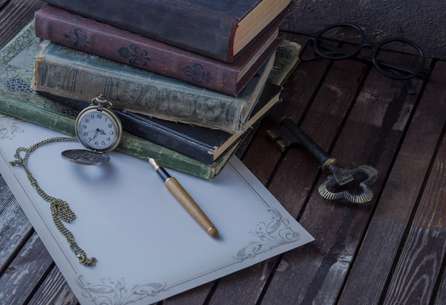 On the table are old books, pocket watches, fountain pen, glasses and writing paper