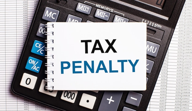 On the table are reports, a calculator and a card with the words tax penalty on it