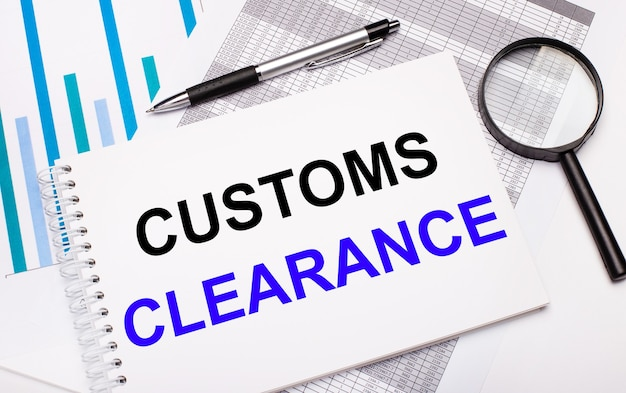 On the table are reports, diagrams, a pen, a magnifying glass and a white notepad with customs clearance text. business concept