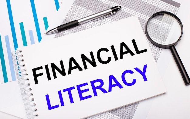 On the table are reports, diagrams, a pen, a magnifying glass and a white notepad with financial literacy text. business concept