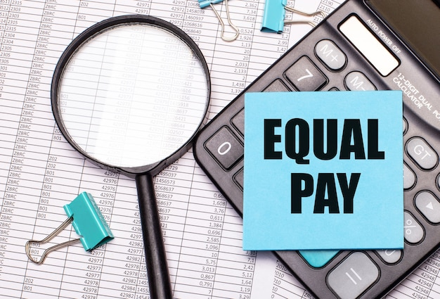 On the table are reports, a magnifying glass, a calculator, and a blue note sticker with the words equal pay. business concept