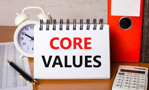 On the table are reports, a white alarm clock, a calculator, folders for papers, a pen and a white notebook with the text core values. business concept