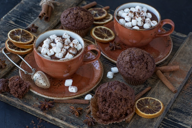 On the table are two cups of hot cocoa and marshmallows, chocolate muffins and decor