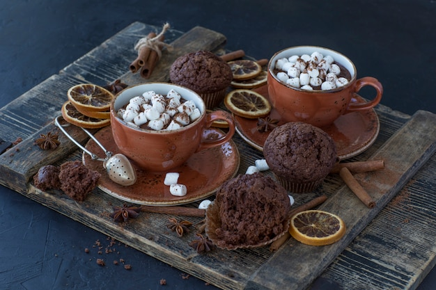 On the table are two cups of hot cocoa and marshmallows, chocolate muffins