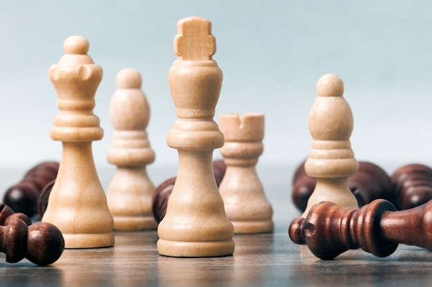 On the table are white chess pieces. the king's figure is in focus in the center; the remaining figures are out of focus. around them are black pieces. the concept of business,