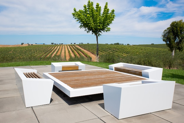 Table and armchairs on terrace with countryside landscape