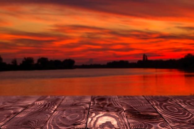 あなたの装飾とぼやけた夕焼け空の風景のための空きスペースのテーブルの背景。水面からの日の出。