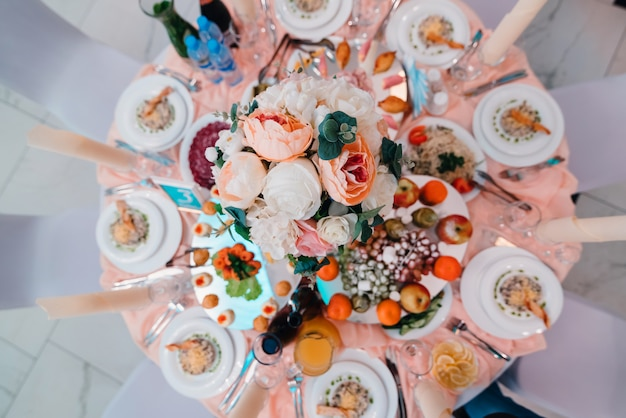 Table beautifully decorated in restaurant with different food for dinner