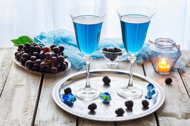 On the table a blue drink in transparent glasses, grapes and a candle in a blue candlestick