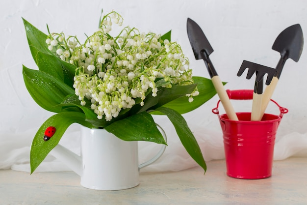 On the table a bouquet of lilies of the valley is placed in a watering can and a bucket