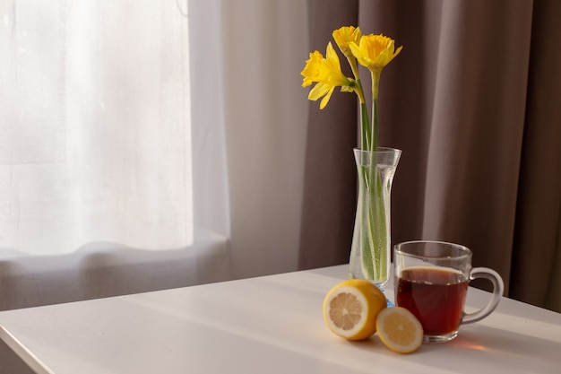 Table by the window with white and brown curtains is a cup of tea, lemon and yellow daffodils in a glass vase.