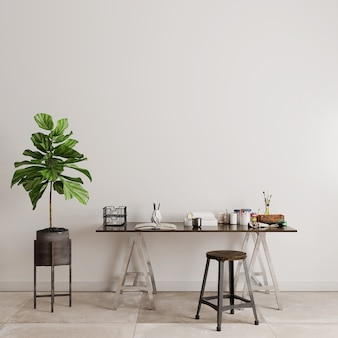 Table and chairs with green plants in front of the white wall
