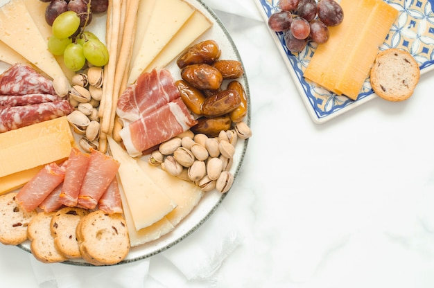 Table of cheeses and sausages accompanied by grapes and nuts.