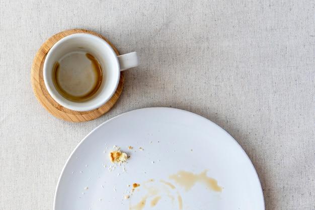 에스프레소용 커피 컵이 있는 식탁보로 덮인 테이블, 디저트 부스러기가 있는 접시, 위쪽 전망, 평평한 평지