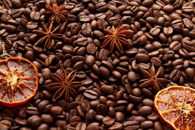 A table covered with coffee beans with anise stars and dried oranges. background for a coffee menu.