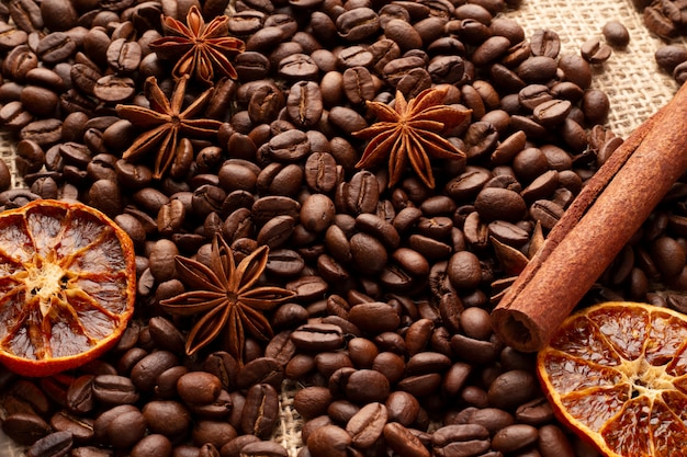 A table covered with coffee beans with cinnamon, anise stars and dried orange.