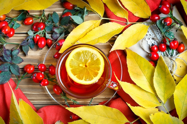 Table decorated with autumn leaves, berries and fresh tea